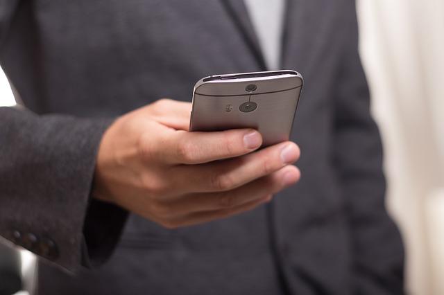 muž v saku s mobilem.jpg
